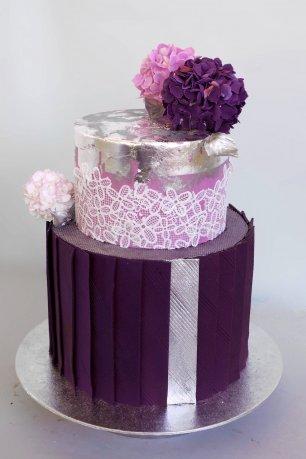 Небольшой торт, сочетающий множество разных текстур: плиссе из текстурированных сахарных панелей, белое сахарное кружево, листовое пищевое серебро и серебряный порошок. Сахарные гортензии в трех разных оттенках