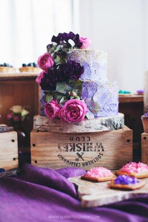 Сиреневый свадебный торт, украшенный цветами