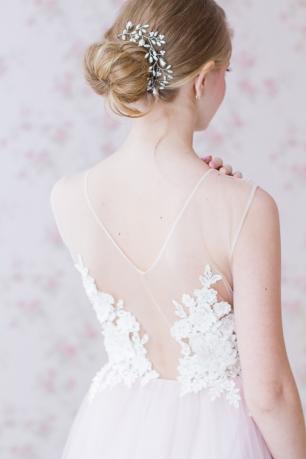 Элегантный гладкий пучок, украшенный скромной жемчужной веточкой, идеален для лаконичного свадебного образа!