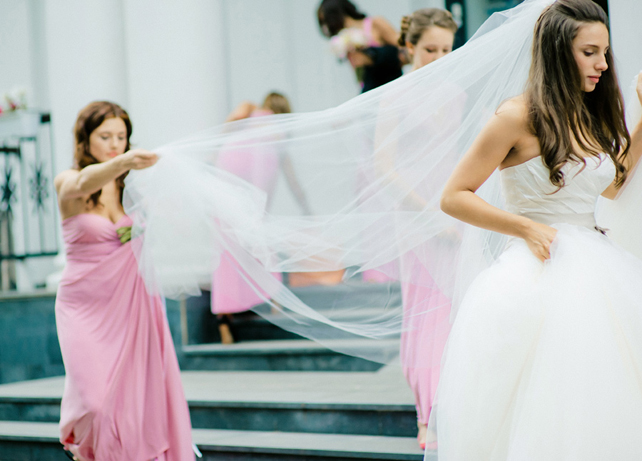 Подружка держит фату невесты
